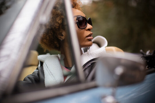 Young woman in sunglasses driving convertible
