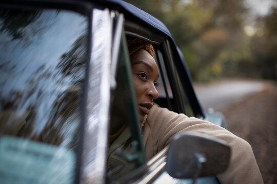 Beautiful serene young woman in car window