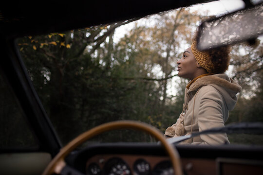 Serene beautiful young woman outside convertible in autumn park