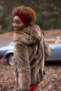 Portrait happy young woman in fur coat in autumn park
