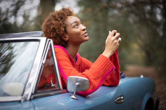 Young woman with digital camera looking up in convertible