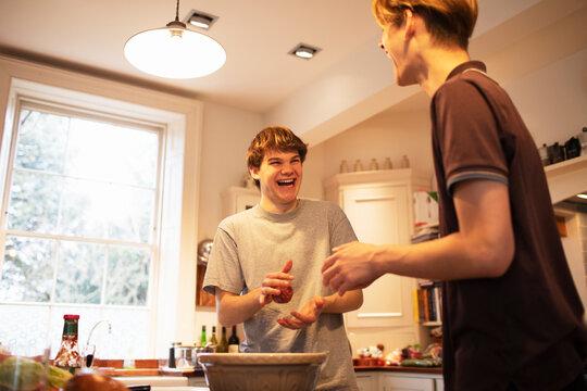 Happy teenage boys making hamburger patties in kitchen