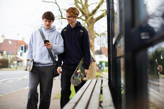 Teenage boys with skateboards and smart phone at bus stop