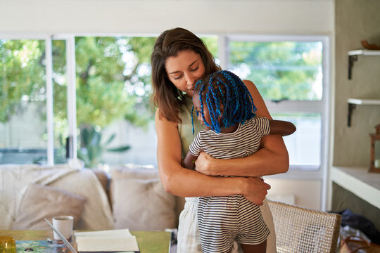 Affectionate mother hugging daughter at home