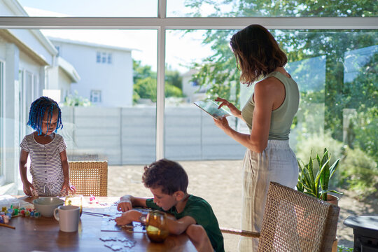 Mother and kids working and playing at dining table