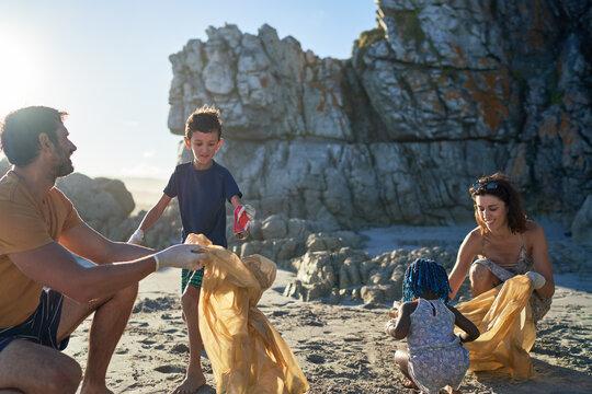 Family volunteering picking up litter on sunny summer beach