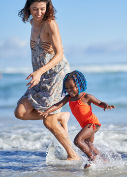 Happy mother and toddler daughter running in sunny ocean surf