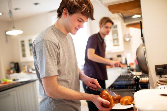 Teenage boy slicing hamburger buns in kitchen