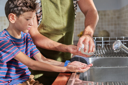 Father and son washing hands with soap at kitchen sink
