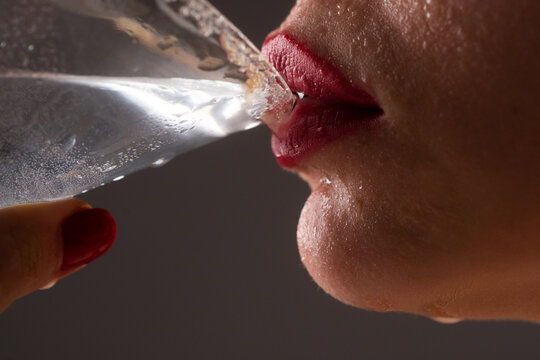 Woman drink cocktail. Close up wet sexy lips. Young girl drinking red lip cocktail closeup.