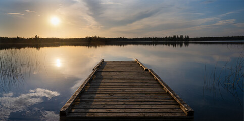 Evening sun lights up clouds and an old wooden dock in a calm lake.