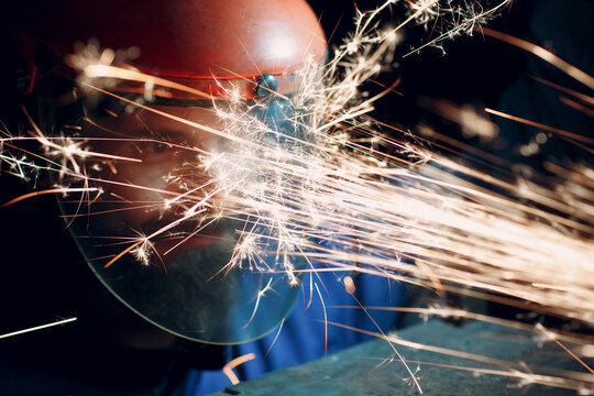 Worker in transparent protective mask works on metal with circular grinder saw. Sparks and face