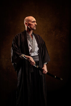 View of a blind and bald man wearing a kimono holding a katana in his hands