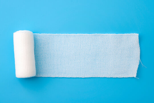 First aid, injury protecting wrapping and wound dressing concept clean cotton gauze bandage isolated on blue background with copy space