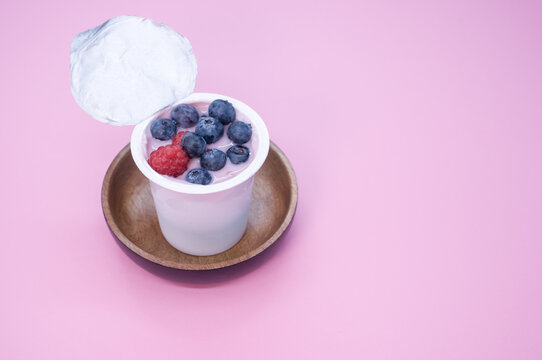 Top view of a berry yogurt in a plastic cup on a pink background