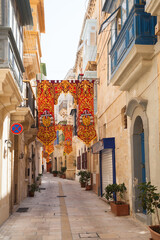 Old narrow street, perspective view with colorful flags decoration, Valletta