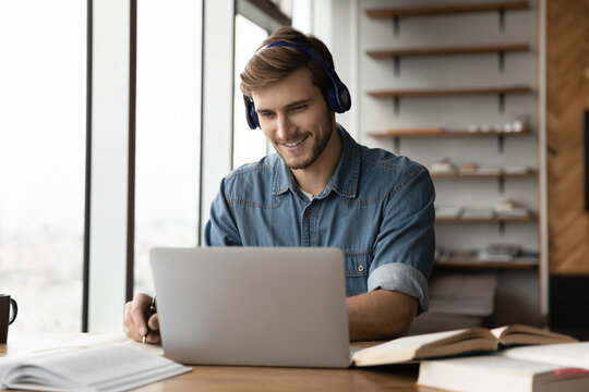 Smiling young handsome man in wireless headphones listening educational webinar lecture on computer, writing notes, improving professional knowledge, studying on online courses in modern home office.