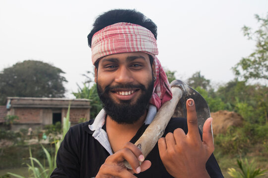 Portrait of a Young Adult Farmer holding a Shovel with voters mark on finger in agricultural field