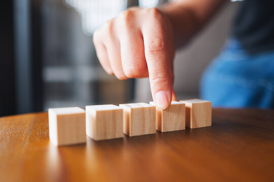 Closeup image of a hand choosing and picking five pieces of blank wooden cube block