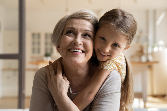 Joyful small 7s kid girl cuddling from back laughing old middle aged grandmother, enjoying tender sweet moment together at home. Happy older retired woman spending weekend with little granddaughter.