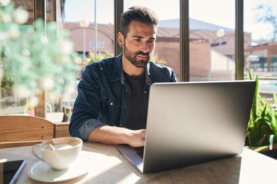 Ethnic freelancer working on laptop at restaurant table