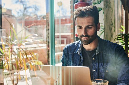 Masculine ethnic entrepreneur typing on laptop in restaurant