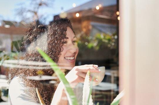 Dreamy ethnic woman enjoying coffee in restaurant