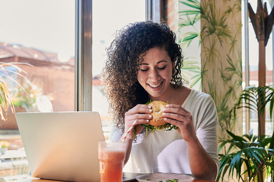 Smiling ethnic freelancer with delicious bagel sandwich against laptop indoors