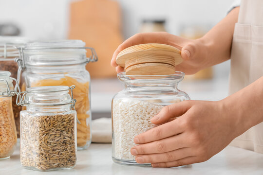 Female hands and jars with different products in kitchen, closeup