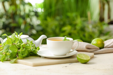 Board with cup of tasty green tea, pot and ingredients on table outdoors