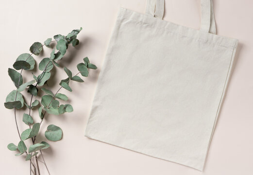Mockup empty template White cream shopping bag for your design, eco friendly, zero waste with copy space. Eucalyptus branches. Flat lay.