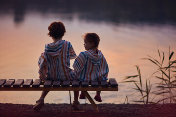 Fototapeta cute children, siblings sitting on the bench by the lake at warm summer evening obraz