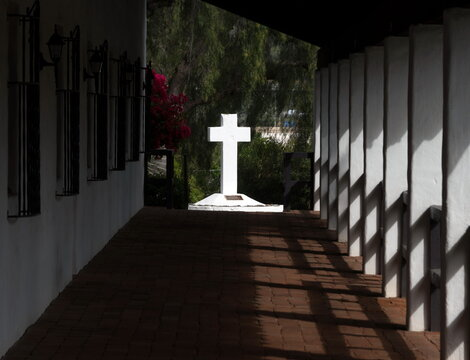 Shades in gallery in front of Mission Basilica San Diego De Alcala lea leading to bright white cross