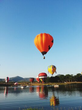 Hot Air Balloon Flying Over Water Against Clear Sky
