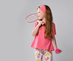 Smiling active red-haired kid girl in pink t-shirt and colorful pants is going to play outdoor...