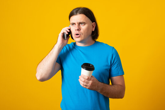 Handsome man with a serious  expression, talking on a cell phone, drinking coffee to go, wearing a blue t-shirt, on a yellow background.