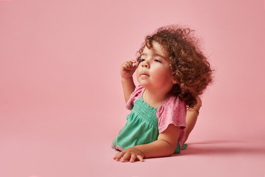 Cute little girl with raised leg on pink background