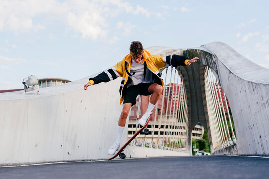 Caucasian teenager jumping with skateboard on the bridge in the city
