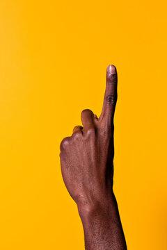 Black man raising index finger against yellow background