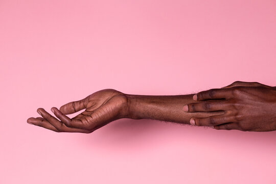Black man touching his forearm with hand on pink background