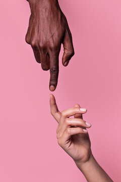 Opposed hands of african-american man pointing at each other wit index finger isolated on pink background