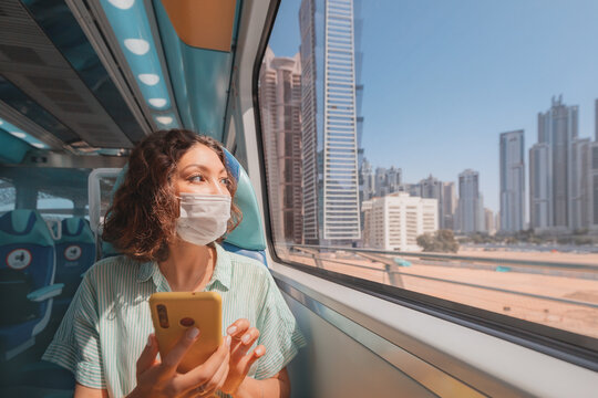 Woman in a protective medical mask rides the subway, holds a smartphone in her hands and looks out the window where the giant skyscrapers of Dubai rise