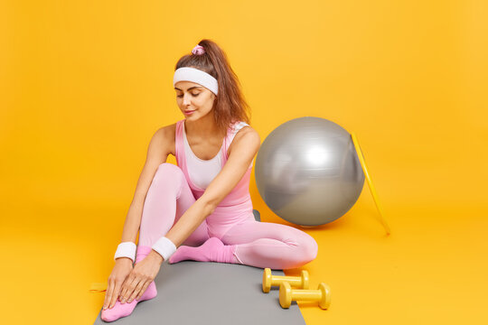 Young fit sportswoman with pony tail leans to legs stretches before workout wears headband wristbands uses sport equipment isolated over yellow background. People fitness and wellness concept