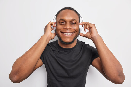 Cheerful handsome man with dark skin smiles broadly enjoys listening music via wireless headphones wears black t shirt isolated over white background. People lifestyle entertainment concept.