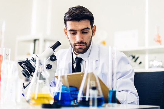 Professional scientist man research and working doing a chemical experiment while making analyzing and mixing liquid in test tube.Young science man looking sample chemical on glass at laboratory