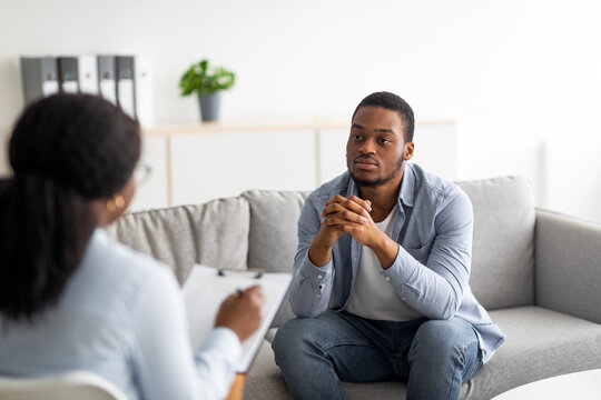 Psychological help service. Depressed male patient having psychotherapy session with counselor at mental health clinic