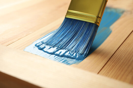 Applying blue paint onto wooden surface, closeup