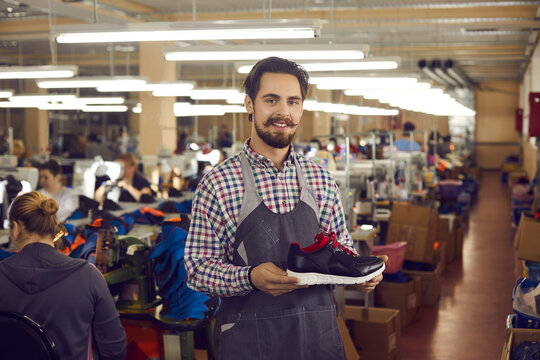 Young male shoemaker designerwith friendly smile on face wearing apron presenting new sports sneakers shoe collection. Trendy modern footwear production, logistics and distribution