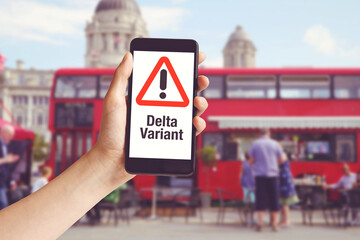 Hand holding mobile phone with with warning message delta variant and red bus