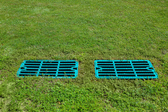 manhole drainage grates on the lawn with green grass septic tank cover, sump cesspool drainage system environment design with copy space, nobody.